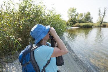 Germany, Usedom, Rankwitz, Lieper Winkel, woman with binoculars watching something - SIEF07297