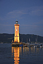 Germany, Lindau, Harbour entrance with lighthouse at sunset - AXF00797