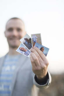 Man's hand holding four instant photos of himself, close-up - SKCF00263