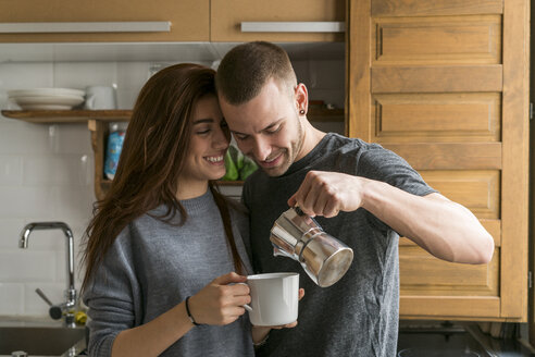 Amorous couple standing in kitchen, drinking coffee - KKAF00450