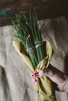 Woman's hand holding bunch of chives wrapped in paper - GIOF01927