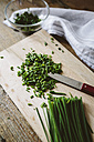 Chopped and whole chives and kitchen knife on wooden board - GIOF01933