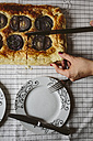 Woman cutting baked Focaccia with red onions , close-up - GIOF01945