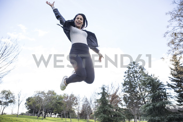 Portrait of smiling young woman jumping in the air - ABZF01939