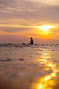 Indonesia, Bali, female surfer in the ocean at sunset - KNTF00635