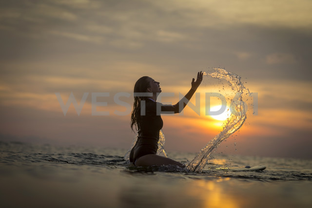 Indonesia, Bali, female surfer in the ocean at sunset - KNTF00638