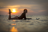 Indonesia, Bali, female surfer in the ocean at sunset - KNTF00641