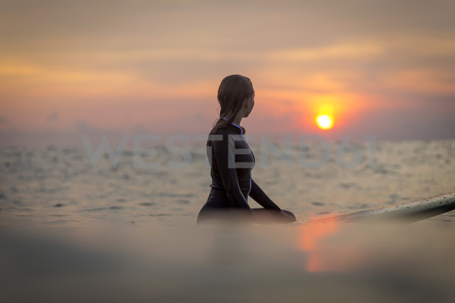 Indonesia, Bali, female surfer in the ocean at sunset - KNTF00644