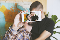 Young gay couple taking a selfie with smartphone, close-up - RTBF00688