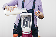 Pregnant woman pouring milk into a blender for preparing smoothie, partial view - JRFF01208