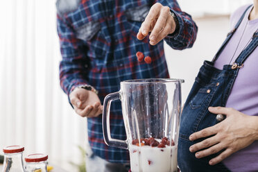 Couple preparing smoothie with raspberries, partial view - JRFF01214