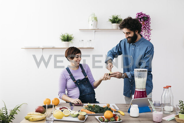 Smiling ccouple preparing healthy smoothies with fresh fruits and vegetables - JRFF01232