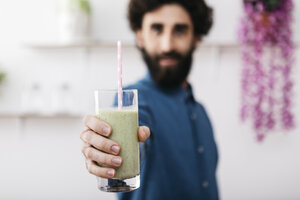 Man's hand holding glass of green smoothie, close-up - JRFF01235