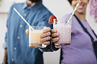 Couple with glasses of different  smoothies ready to drink, partial view - JRFF01241