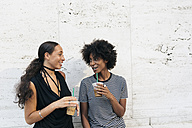 Two friends with drinks talking in front of a wall - GIOF01948