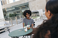 Portrait of smiling woman sitting at pavement cafe talking to her friend - GIOF01957