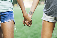 Two women holding hands in a park - GIOF01975