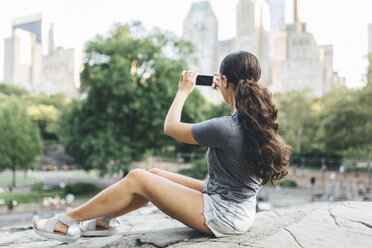 USA, Manhattan, young woman sitting in Central Park taking picture  of skyline with smartphone - GIOF01999