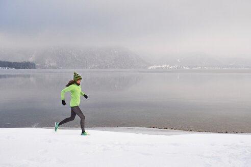 Germany, Bavaria, Lake Kochel, woman jogging in winter - MRF01688