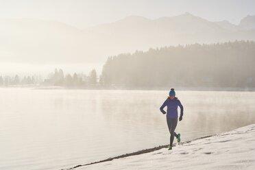 Germany, Bavaria, Lake Walchen, woman jogging in winter - MRF01691