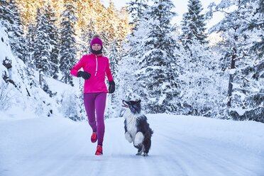 Austria, Tyrol, Karwendel, Riss Valley, woman jogging with dog in winter forest - MRF01697