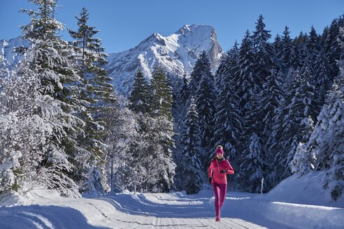 Austria, Tyrol, Karwendel, Riss Valley, woman jogging in winter forest - MRF01700