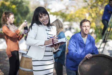 Wine saleswoman with group of clients outdoors and wine worker with barrel - ZEF12879