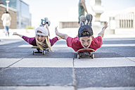 Kids skateboarding in the street, lying on belly - ZEF12906