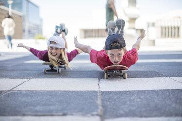 Kids skateboarding in the street, lying on belly - ZEF12906