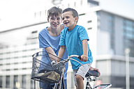 Boy teaching little brother how to ride a bycicle - ZEF12909
