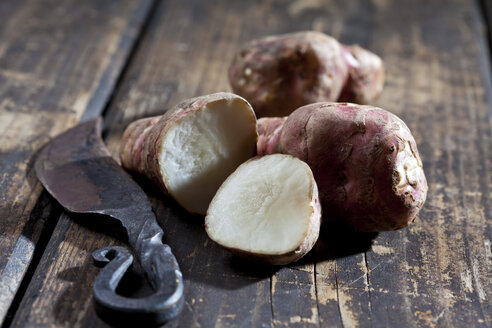 Whole and sliced Jerusalem artichoke and an old knife on wood - CSF27885