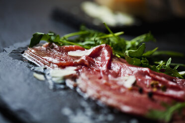 Beef Carpaccio with rocket, olive oil, parmesan, pepper and salt on slate - CSF27906