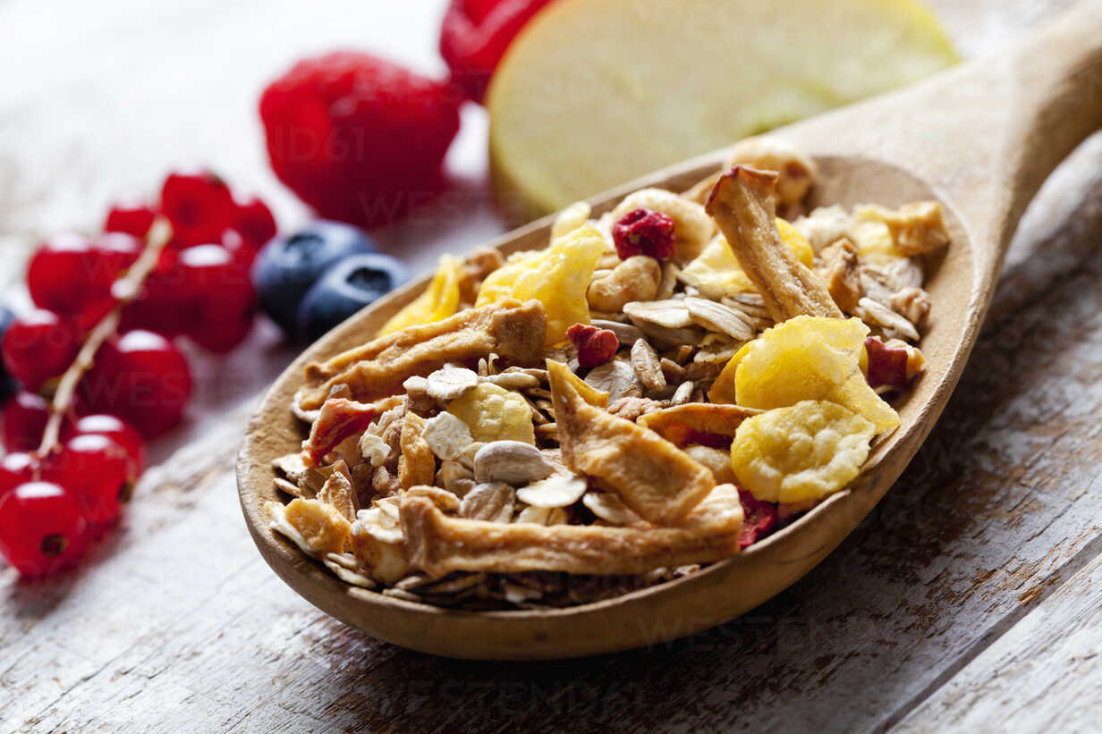 Wooden spoon of granola with dried fruits and various fresh fruits on wood - CSF27918 - Dieter Heinemann/Westend61