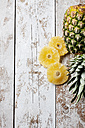 Pineapple and dried rings of pineapple on wood - CSF27930