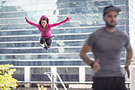 Man running and woman jumping in the city - ZEF12923