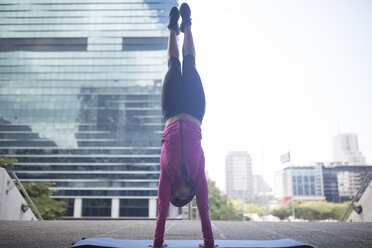 Young woman doing a handstand on gymnastics mat in the city - ZEF12932