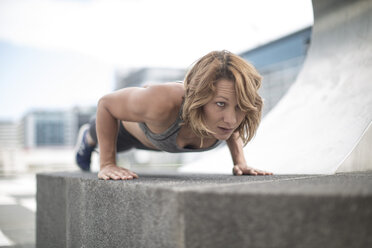 Young woman doing push-ups in the city - ZEF12938