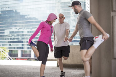 Three athletes stretching in the city - ZEF12941