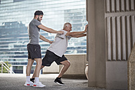 Fitness instructor guiding senior man doing a stretching exercise - ZEF12944