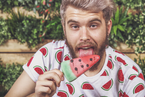 Portrait of young man eating watermelon ice lolly on terrace - RTBF00691