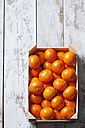 Tangerines in crate, on white, wooden background - CSF27937