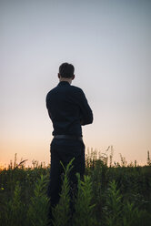 Businessman standing in rural field at sunset - KNSF01051