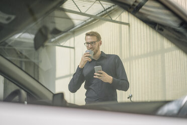 Smiling businessman holding cell phone and cup of coffee - KNSF01066