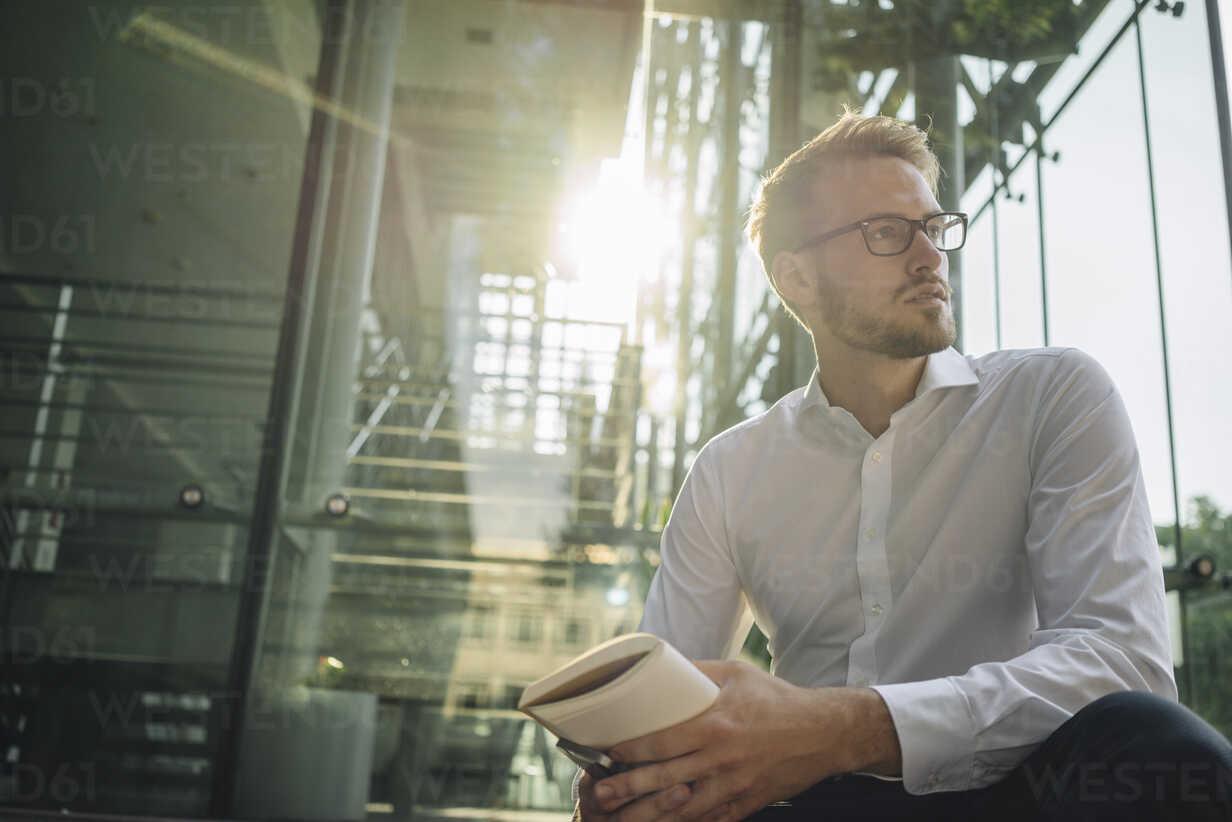 Businessman holding book looking away - KNSF01072 - Kniel Synnatzschke/Westend61