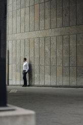 Businessman standing at a wall - KNSF01105