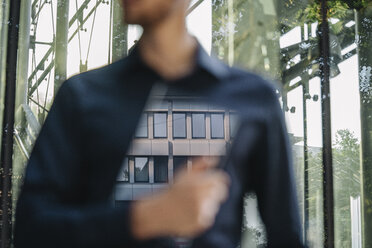 Businessman holding futuristic portable device with reflection of office building - KNSF01114