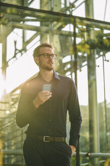 Businessman holding smartphone outdoors - KNSF01120