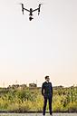 Drone flying above businessman - KNSF01129