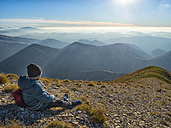 Italy, Marche, Boy watching Apennines at sunset - LOMF00516