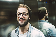 Portrait of a young man in an elevator - RAEF01739